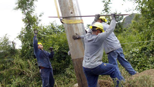 Trabajadores puertorriqueños arreglando un poste eléctrico en Ponce - Sputnik Mundo