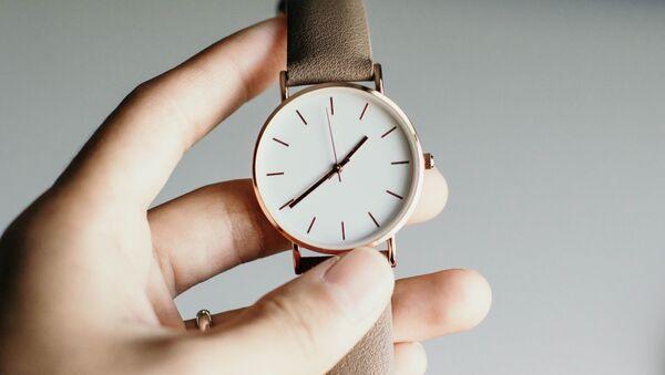 Una persona sostiene un reloj - Sputnik Mundo