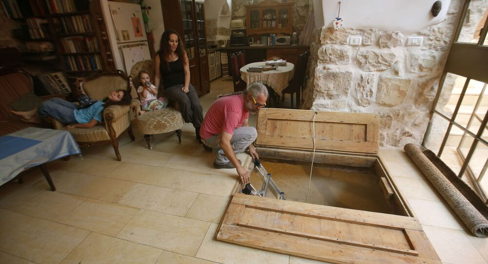 Tal coloca una escalera desde su sala de estar el 1 de julio de 2015, que conduce a un antiguo baño ritual judío (mikve), que data del período del Segundo Templo y que se cree que tiene más de 2000 años de antigüedad.