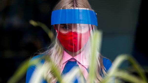 Una mujer con una máscara protectora y una mascarilla para protegerese del COVID-19 en Moscú (archivo) - Sputnik Mundo