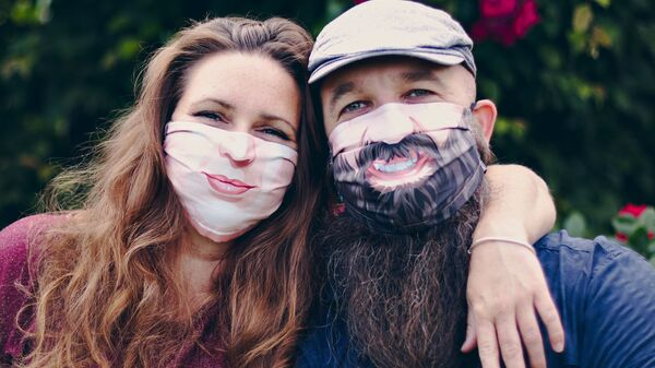 Una pareja con divertidas mascarillas - Sputnik Mundo