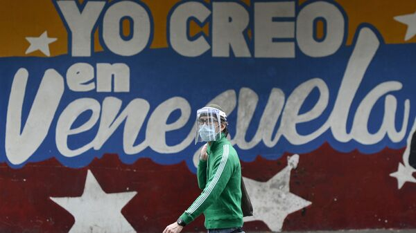 Un hombre pasa al lado de un mural en Caracas que dice yo creo en Venezuela - Sputnik Mundo