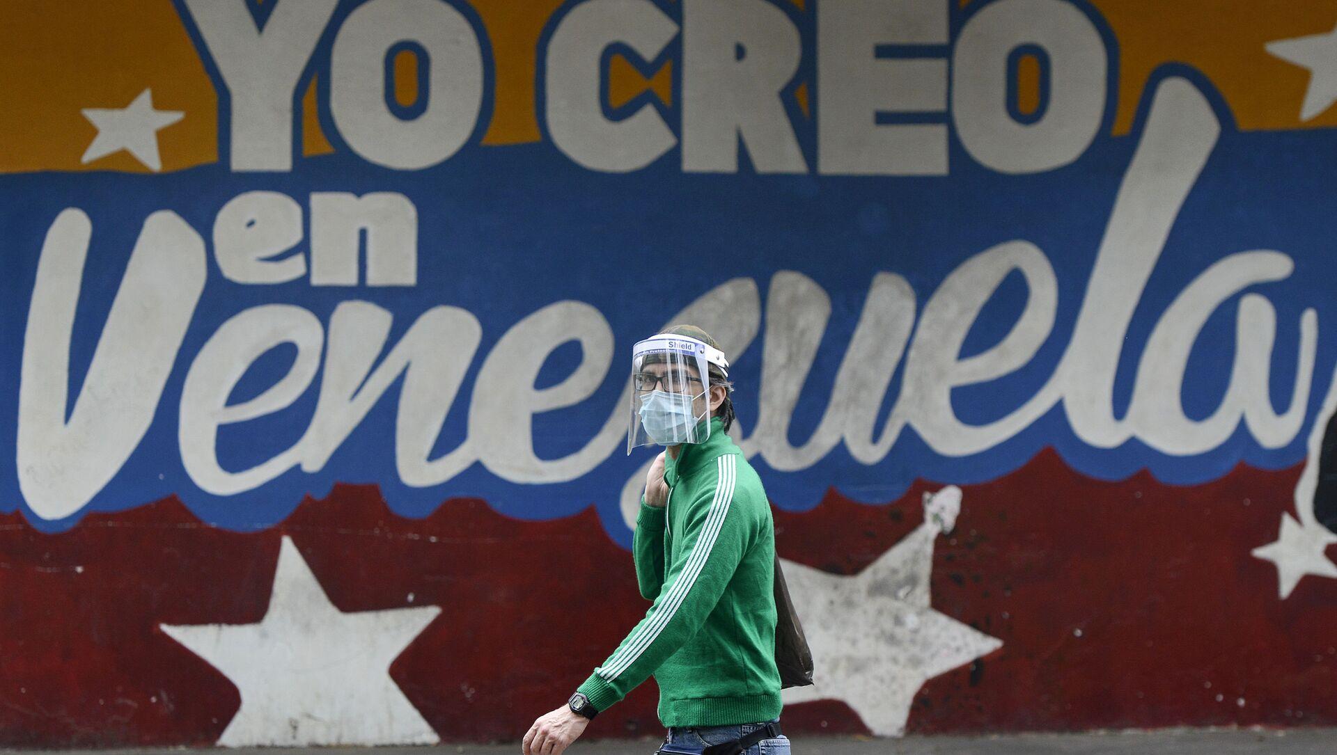 Un hombre pasa al lado de un mural en Caracas que dice yo creo en Venezuela - Sputnik Mundo, 1920, 02.10.2020