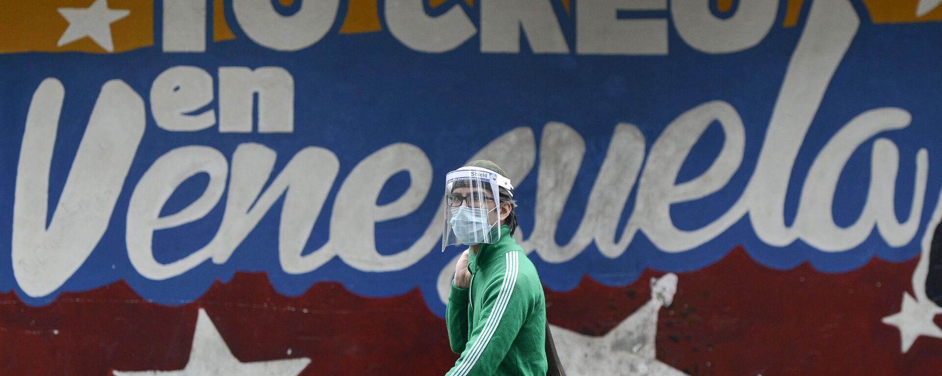 Un hombre pasa al lado de un mural en Caracas que dice yo creo en Venezuela - Sputnik Mundo, 1920, 27.05.2021