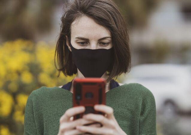 Mujer con mascarilla usando el celular