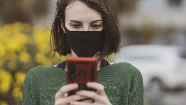 Mujer con mascarilla usando el celular - Sputnik Mundo