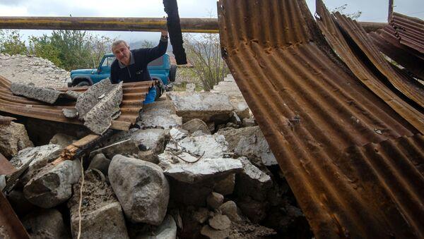 Мужчина у хозяйственной постройки, разрушенной в результате обстрела общины Иванян Нагорного Карабаха - Sputnik Mundo