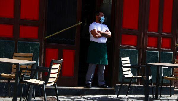 Un camarero con mascarilla esperando clientes en una terraza de Madrid - Sputnik Mundo
