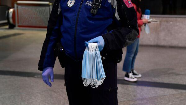 Un Policía reparte mascarillas en la estación de Atocha de Madrid - Sputnik Mundo