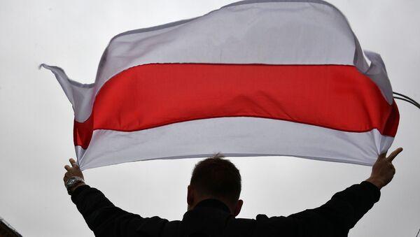 Un manifestande con la bandera opositora de Bielorrusia - Sputnik Mundo