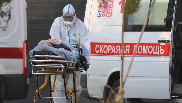 Un médico ruso transporta a un paciente con coronavirus - Sputnik Mundo