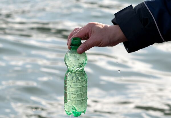 Сотрудник Следственного комитета России по Камчатскому краю берет пробу морской воды - Sputnik Mundo