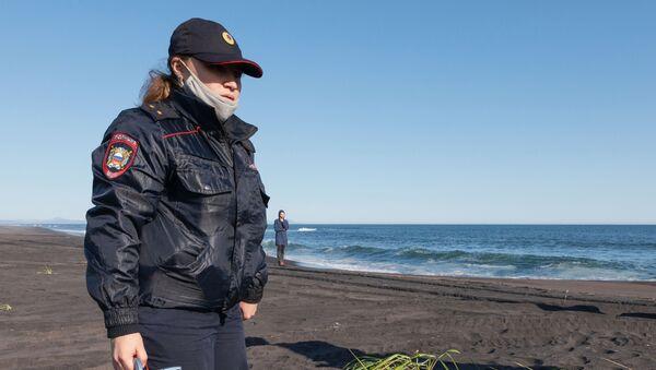 Сотрудник УМВД Камчатского края во время оперативно-разыскных мероприятий на месте предполагаемого происшествия на Халактырском пляже на Камчатке - Sputnik Mundo