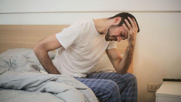 Un hombre sentado en la cama (imagen referencial) - Sputnik Mundo