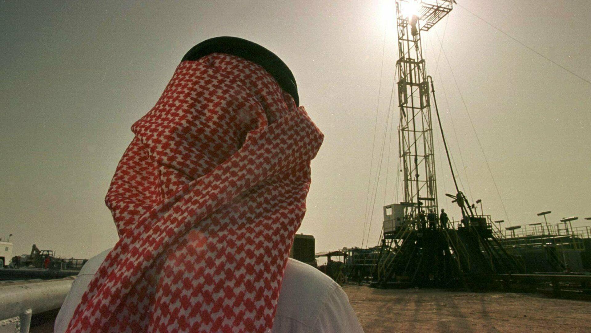 Un empleado de la compañía petrolera saudí Aramco observa el progreso de una plataforma situada en un yacimiento petrolero  - Sputnik Mundo, 1920, 01.03.2021