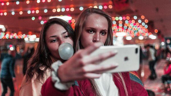 Dos chicas con un smartphone (imagen referencial) - Sputnik Mundo