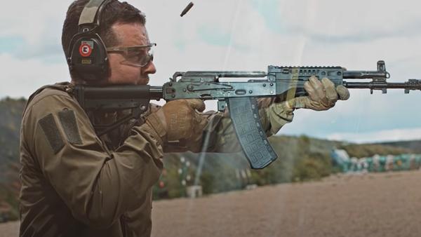 Un hombre dispara un arma de Kalashnikov - Sputnik Mundo