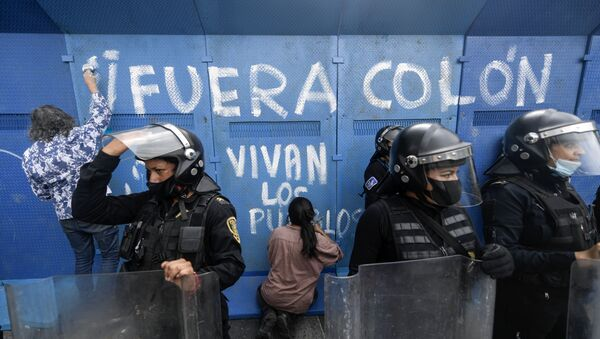 Los manifestantes hacen un graffiti en una valla metálica que rodea la estatua de Cristobal Colón para su protección, CDMX - Sputnik Mundo