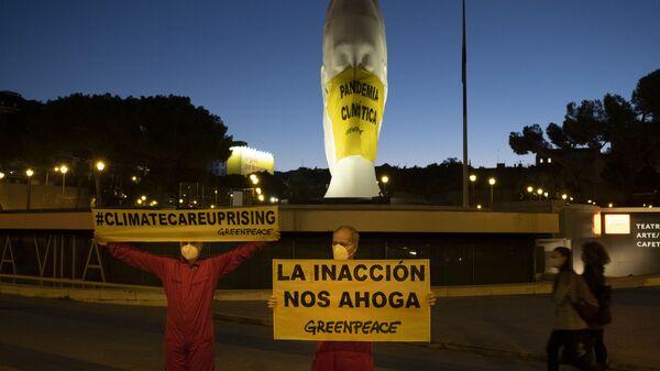 Activistas de Greenpeace colocan una mascarilla a una escultura gigante en la Plaza Colón  - Sputnik Mundo