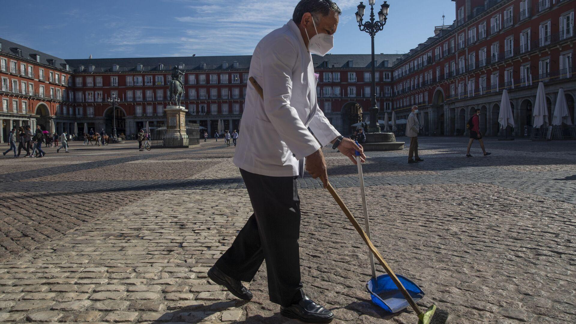 Un camarero con mascarilla limpiando en una de las terrazas de la Plaza Mayor de Madrid - Sputnik Mundo, 1920, 10.03.2021