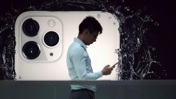 Una persona con un celular y un Iphone 11 Pro en el fondo - Sputnik Mundo