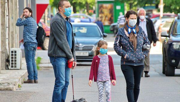 Una familia con mascarillas (imagen referencial) - Sputnik Mundo