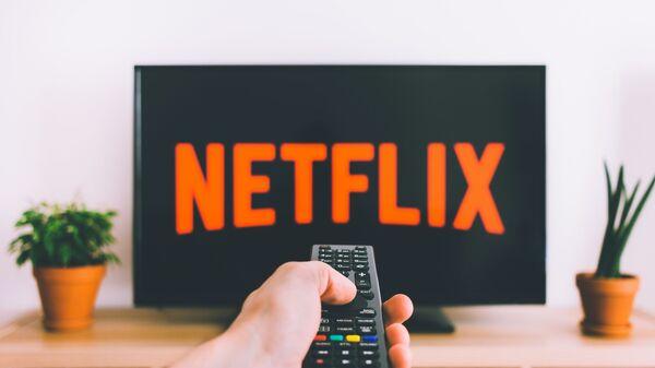 Una persona apunta con el control remoto a una pantalla de televisión con el logotipo de Netflix - Sputnik Mundo