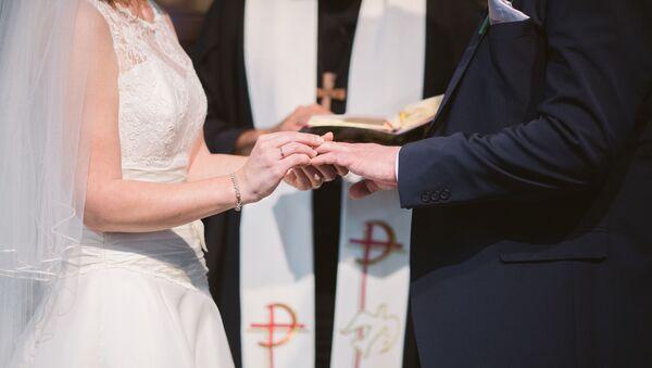 Una mujer pone un anillo de bodas en el dedo de su marido (archivo) - Sputnik Mundo