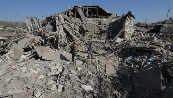 Unos hombres en medio de las ruinas de una casa en Stepanakert, el 17 de octubre de 2020 - Sputnik Mundo
