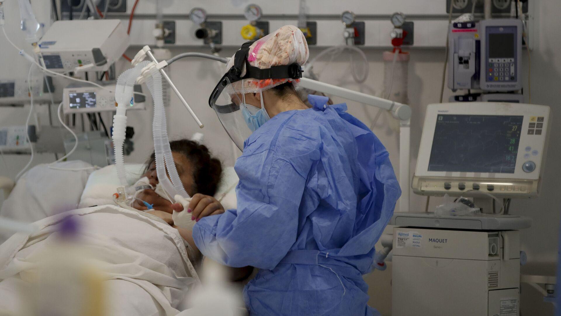 Una trabajadora de la salud atiende a un paciente en una unidad de cuidados intensivos designada para personas infectadas con coronavirus en un hospital en Buenos Aires (Argentina) - Sputnik Mundo, 1920, 14.04.2021