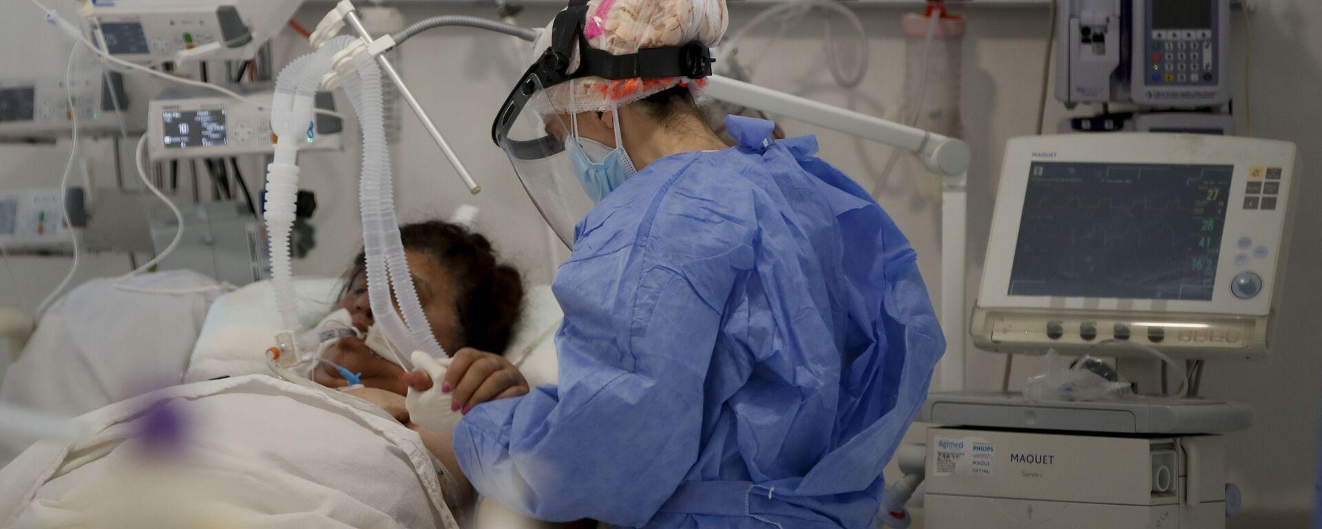Una trabajadora de la salud atiende a un paciente en una unidad de cuidados intensivos designada para personas infectadas con coronavirus en un hospital en Buenos Aires (Argentina) - Sputnik Mundo, 1920, 22.06.2021