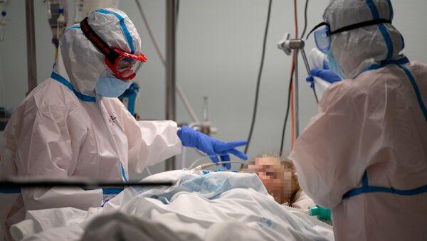 Los médicos atienden a un paciente con COVID-19 - Sputnik Mundo
