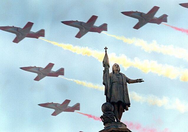 Un grupo de aviones españoles CASA C-101 sobrevuela la estatua de Cristóbal Colón en Madrid