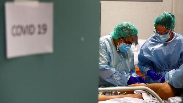 Trabajadores médicos atienden a un paciente infectado por COVID-19 en España - Sputnik Mundo