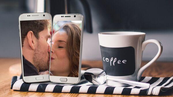 Dos móviles muestran a una mujer y un hombre besándose - Sputnik Mundo