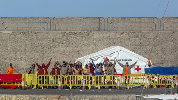 Migrantes gritan libertad junto a las tiendas de la Cruz Roja en las que se alojan unos 400 migrantes en El Puerto de Arguineguín (Gran Canaria) - Sputnik Mundo