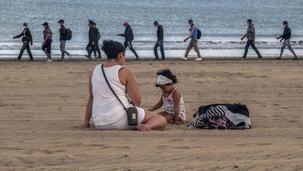 Migrantes caminan por la orilla escoltados por la Policía española tras llegar a la costa de Canarias. 20 de octubre de 2020 - Sputnik Mundo