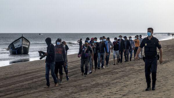 Migrantes de Marruecos caminan por la orilla escoltados por la Policía española tras llegar a la costa de Canarias - Sputnik Mundo