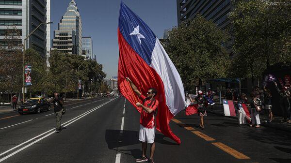 Un manifestante con la bandera de Chile - Sputnik Mundo