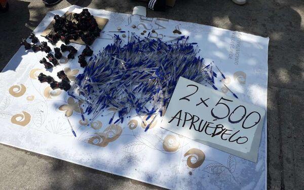 Vendedores ambulantes a las afueras del Estadio Bicentenario vendiendo lápices azules.... y sugiriendo el voto con humor - Sputnik Mundo