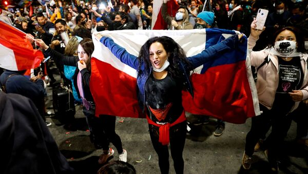 A woman holds a Chilean flag as she reacts to the referendum on a new Chilean constitution in Valparaiso - Sputnik Mundo