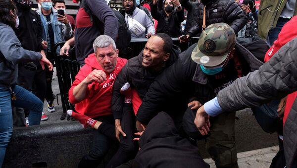 Un hombre protege a un partidario del presidente estadounidense Donald Trump de los manifestantes de la marcha anti-Trump después de los enfrentamientos en el distrito de Manhattan de la ciudad de Nueva York - Sputnik Mundo
