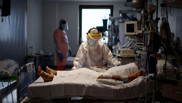 Sanitarios atendiendo a un paciente con coronavirus en España - Sputnik Mundo