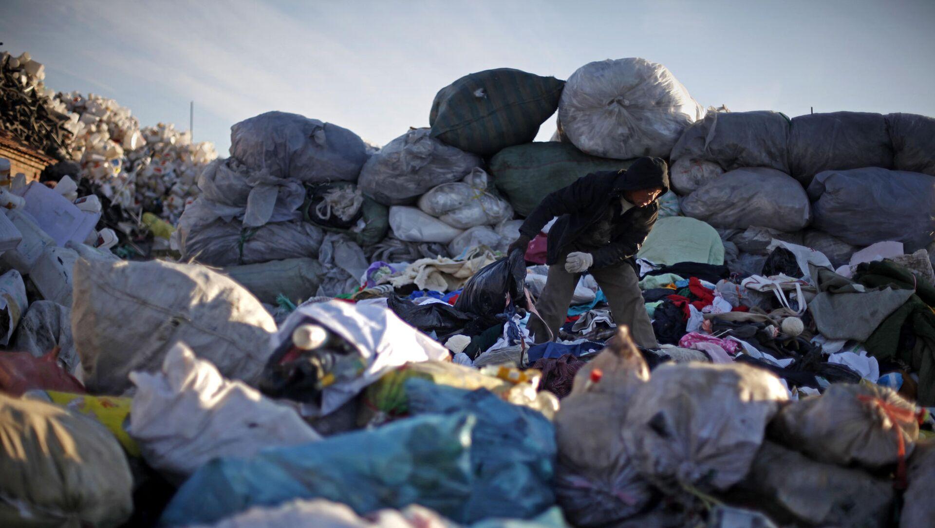 Un hombre chino revisa la ropa desechada en un centro de reciclaje en Pekín, China. - Sputnik Mundo, 1920, 28.10.2020