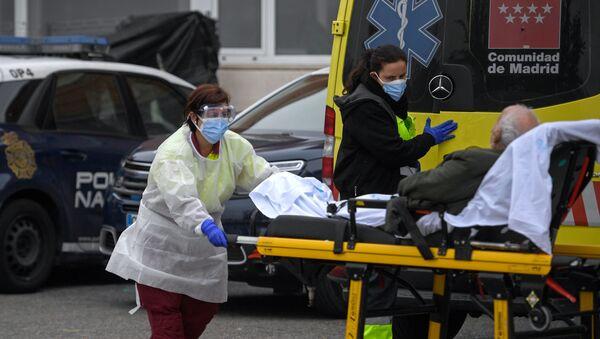 Sanitarias bajando a un paciente de un ambulancia en Madrid - Sputnik Mundo