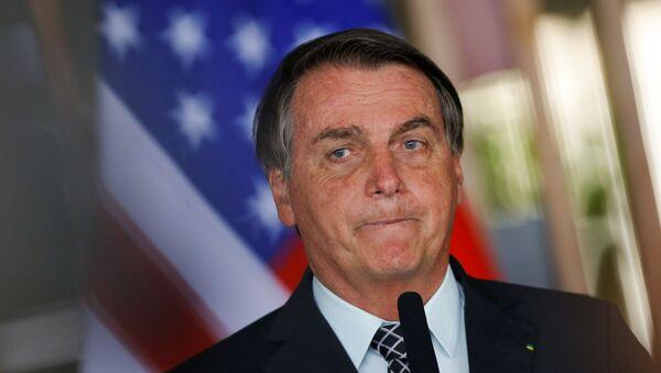 Jair Bolsonaro, presidente de Brasil, junto a la bandera de EEUU - Sputnik Mundo