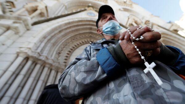 Un hombre reza frente a la iglesia de Notre Dame en Niza, Francia - Sputnik Mundo