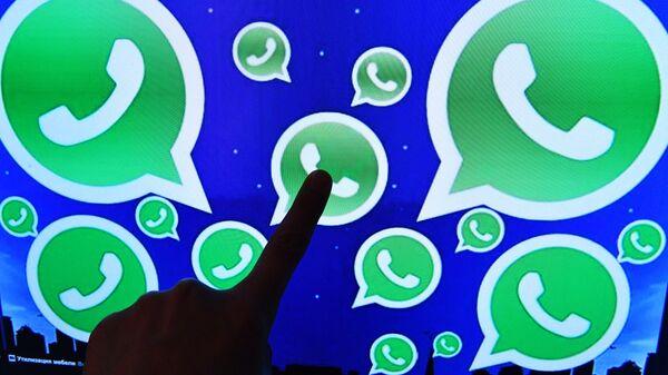 Una persona toca una pantalla en la que se ven diversos logotipos de la aplicación WhatsApp - Sputnik Mundo