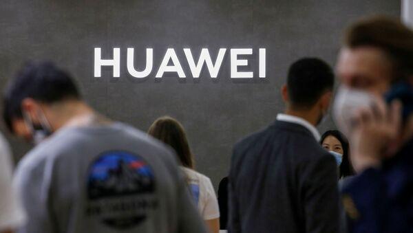 Unas personas caminan delante del estand de Huawei en una feria de tecnología (archivo) - Sputnik Mundo