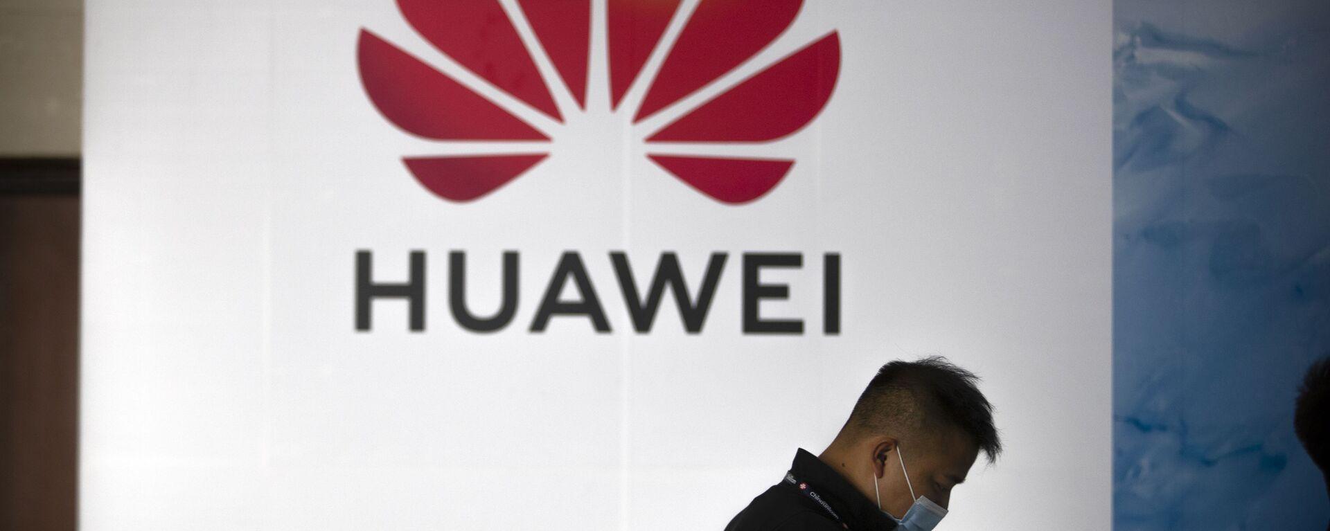 Una persona camina delante del logotipo de Huawei en una feria tecnológica en Pekín - Sputnik Mundo, 1920, 17.12.2020